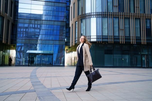 Uma mulher de negócios em um casaco e terno, segurando uma sacola na mão, caminha perto do centro de negócios durante o dia. foto horizontal conceitual