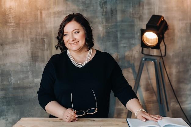 Uma mulher de negócios em um vestido preto com miçangas está em uma mesa em seu escritório.