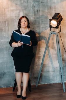 Uma mulher de negócios em um vestido preto frisado fica contra a parede com um livro nas mãos.