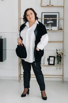 Uma mulher de negócios em uma camisa branca e calças está de pé com um chapéu nas mãos de pé no escritório.