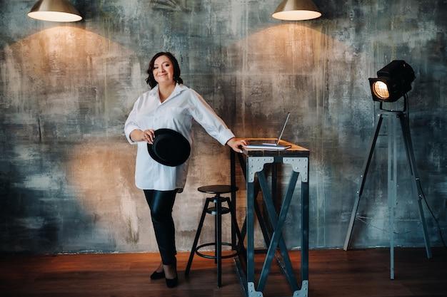 Uma mulher de negócios em uma camisa branca e calças está em seu escritório.