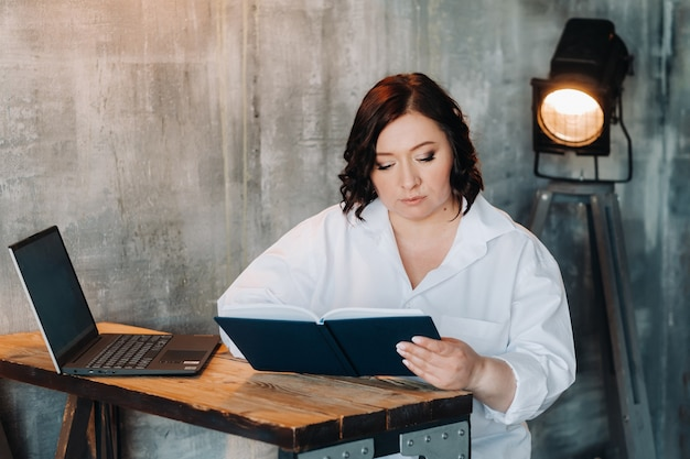 Uma mulher de negócios em uma camisa branca está sentada em uma mesa escrevendo algo em um caderno no escritório.