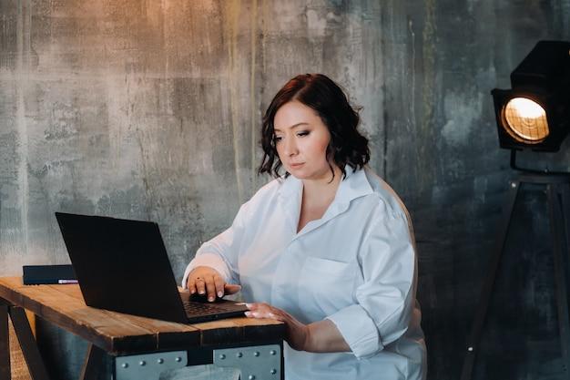 Uma mulher de negócios em uma camisa branca se senta em uma mesa e trabalha em um laptop no interior.