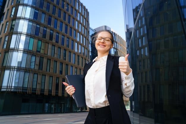 Uma mulher de negócios está com um laptop de terno e óculos do lado de fora de um prédio de escritórios durante o dia.