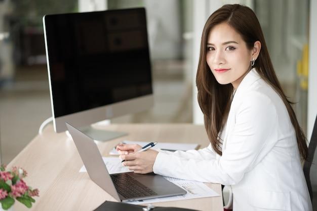 Uma mulher de negócios está sentado em seu escritório. ela é gerente e consultora de seus empregadores.