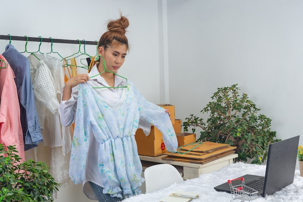 Uma mulher de negócios está trabalhando on-line e tentando responder à embalagem do cliente em casa na parede.