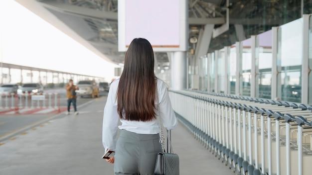 Uma mulher de negócios está usando máscara protetora no aeroporto internacional, viaja sob a pandemia de covid-19
