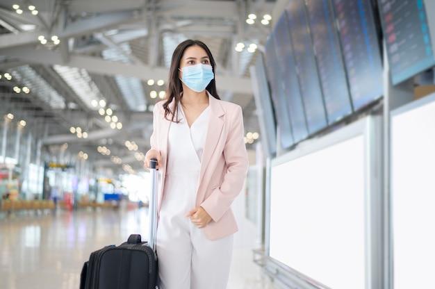 Uma mulher de negócios está usando máscara protetora no aeroporto internacional, viajando sob a pandemia de covid-19,