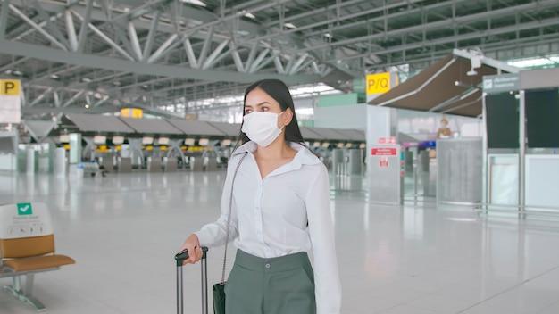 Uma mulher de negócios está usando máscara protetora no aeroporto internacional, viajando sob a pandemia de covid-19
