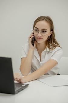 Uma mulher de negócios feliz sentada na mesa atrás de seu laptop