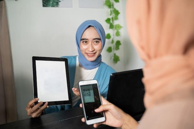 Uma mulher de negócios hijab segura um tablet e mostra a tela para clientes que usam celular enquanto pagam ...