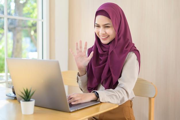 Uma mulher de negócios muçulmana usando fones de ouvido assistindo ao webinar no laptop e fazendo uma videochamada no local de trabalho