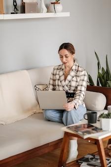 Uma mulher de negócios que tem uma vídeo chamada com um colega que trabalha on-line em casa