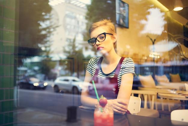 Uma mulher de óculos com um penteado curto senta-se sozinha em um coquetel de restaurante. foto de alta qualidade