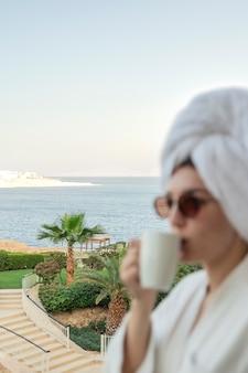 Uma mulher de óculos, com um roupão de banho e uma toalha no hotel, bebe café em uma xícara branca. silhueta desfocada