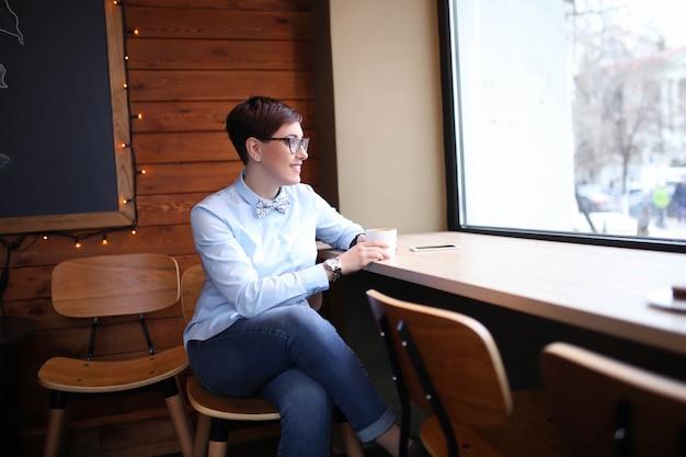 Uma mulher de óculos e cabelos curtos, gerente de negócios, senta-se em um café perto da janela