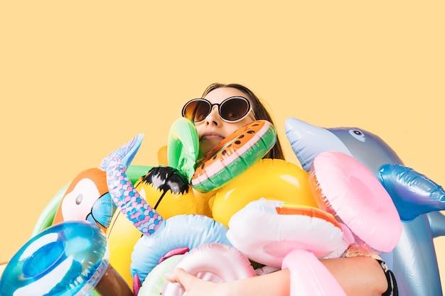 Uma mulher de óculos escuros rodeada por um monte de infláveis de diferentes formas e cores