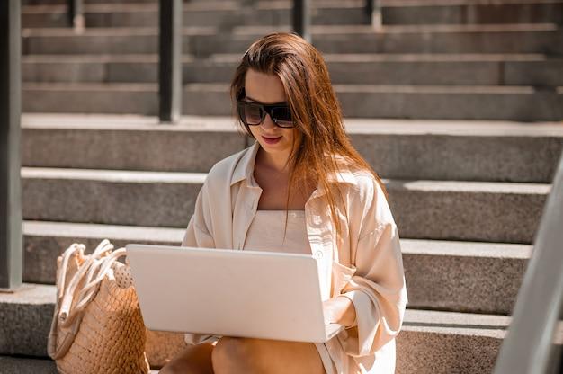 Uma mulher de óculos escuros sentada nos degraus e trabalhando em um laptop