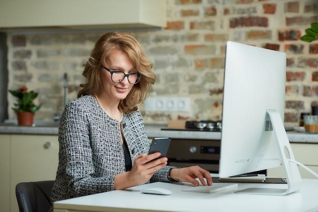 Uma mulher de óculos trabalha remotamente em um computador desktop em seu estúdio. um chefe distraído por um smartphone durante uma videoconferência em casa. um professor feliz usa um telefone celular antes de uma palestra on-line