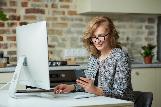 Uma mulher de óculos trabalha remotamente em um computador desktop em seu estúdio. um chefe distraído por um smartphone durante uma videoconferência em casa.