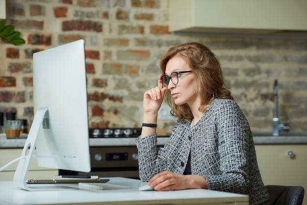 Uma mulher de óculos trabalha remotamente em um computador desktop em seu estúdio. um chefe do sexo feminino à procura de informações em uma videoconferência em casa. uma professora bonita se preparando para uma palestra on-line.