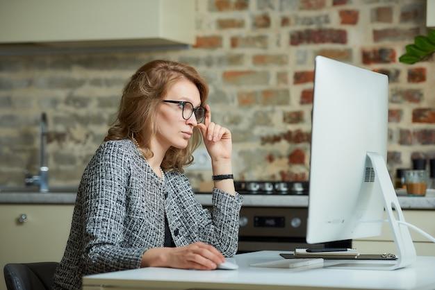 Uma mulher de óculos trabalha remotamente em um computador desktop em seu estúdio. um chefe do sexo feminino à procura de informações em uma videoconferência em casa.