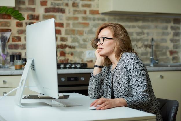 Uma mulher de óculos trabalha remotamente em um computador desktop em seu estúdio. um chefe do sexo feminino ouvindo relatórios de funcionários em uma videoconferência em casa.