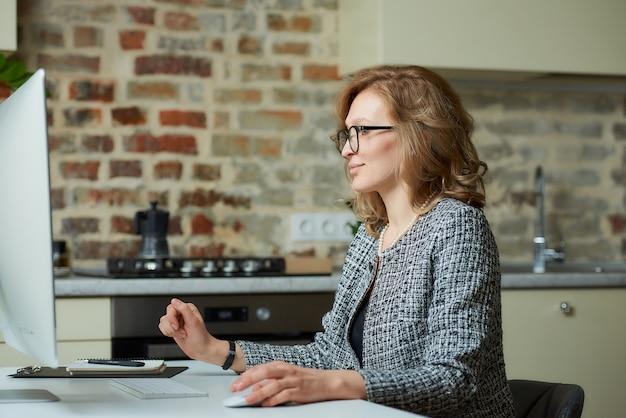 Uma mulher de óculos trabalha remotamente em um computador desktop em seu estúdio. um chefe feliz trabalhando com seus funcionários em uma videoconferência em casa.