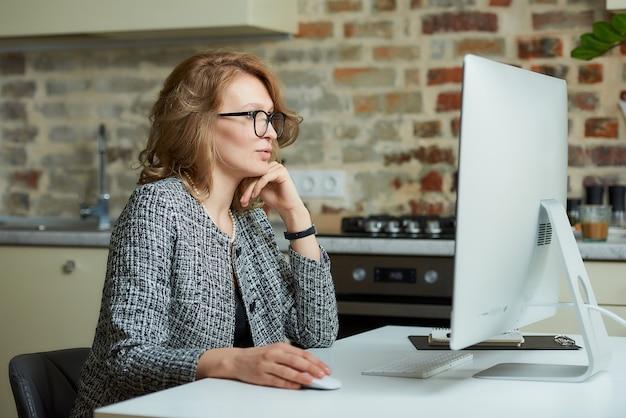 Uma mulher de óculos trabalha remotamente em um computador desktop em seu estúdio. uma chefe do sexo feminino ouvindo um relatório de funcionário em uma videoconferência em casa.