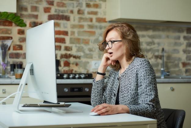 Uma mulher de óculos trabalha remotamente em um computador desktop em seu estúdio. uma chefe é surpreendida pelos funcionários em uma videoconferência em casa. uma professora se preparando para uma palestra on-line.