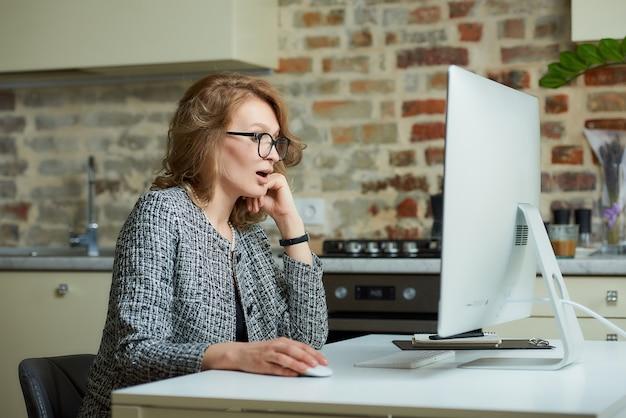 Uma mulher de óculos trabalha remotamente em um computador desktop em seu estúdio. uma chefe é surpreendida pelos funcionários em uma videoconferência em casa.