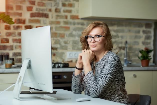Uma mulher de óculos trabalha remotamente em um computador desktop em seu estúdio. uma chefe mulher senta os braços cruzados e pensando durante uma videoconferência em casa.