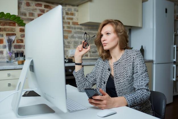 Uma mulher de óculos trabalha remotamente em um computador desktop em seu estúdio. uma senhora usa um telefone durante uma videoconferência em casa.