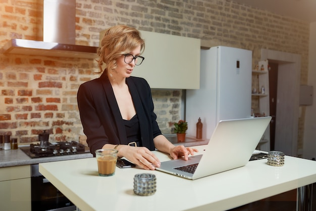 Uma mulher de óculos trabalha remotamente em um laptop na cozinha dela. uma garota em busca de notícias na internet em casa ..