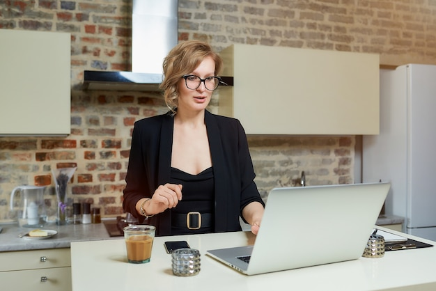 Uma mulher de óculos trabalha remotamente em um laptop na cozinha dela. uma garota gesticulando discute com seus colegas em um briefing de negócios on-line em casa. .