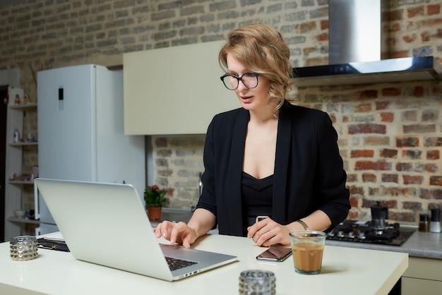Uma mulher de óculos trabalha remotamente em um laptop na cozinha dela. uma garota séria navegando pelas notícias na internet em casa.