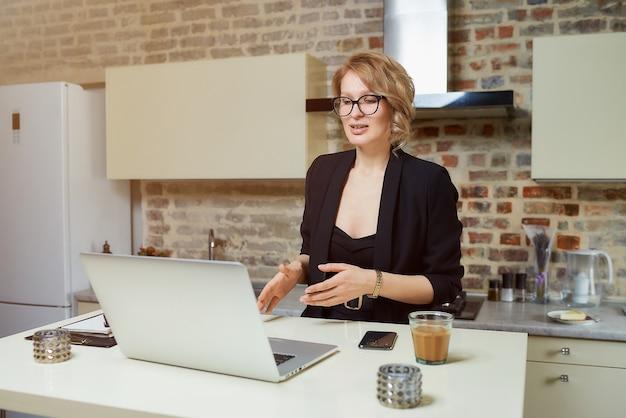 Uma mulher de óculos trabalha remotamente em um laptop na cozinha dela. uma loira gesticulando discute com seus parceiros de negócios em uma videoconferência em casa.
