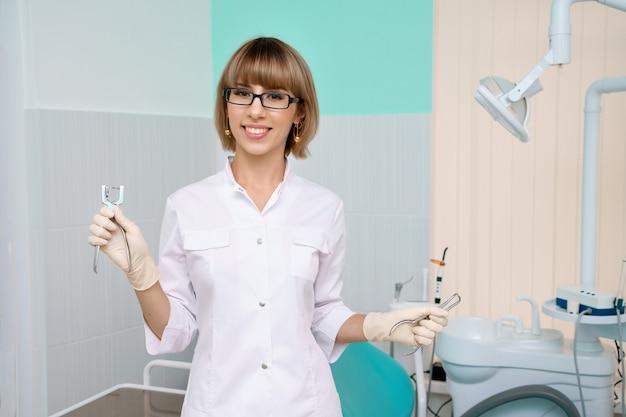 Uma mulher de óculos, um dentista com ferramentas nas mãos em um jaleco branco fica no consultório odontológico e sorri