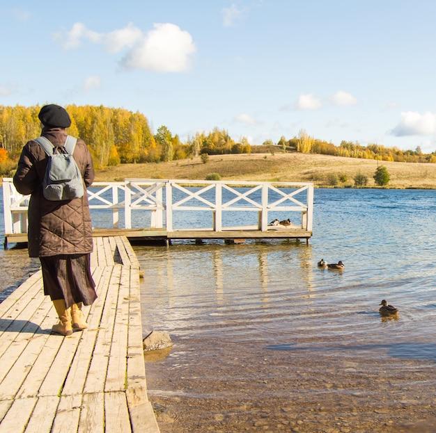 Uma mulher de paletó e botas, com uma mochila, caminha ao longo de um píer de madeira em um parque natural e admira os pássaros. patos na água ao redor.