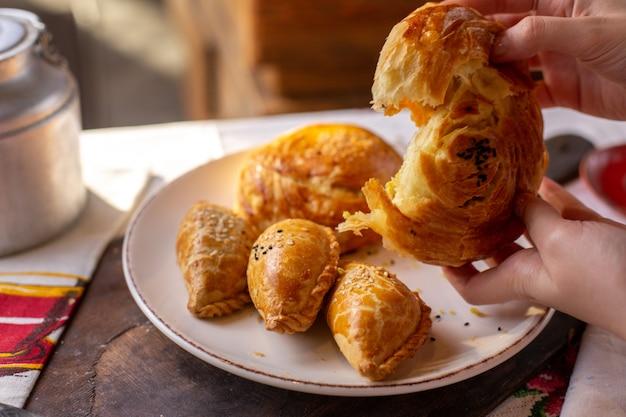 Uma mulher de pastelaria vista frontal rasgando qogal junto com outras padarias biscoitos hora do chá saborosa cerimônia de massa de pão na mesa