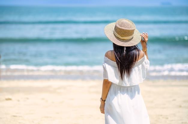 Uma mulher de pé na praia de costas