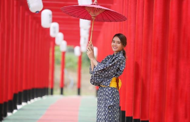 Uma mulher de quimono segurando guarda-chuva entrando no santuário, no jardim japonês.