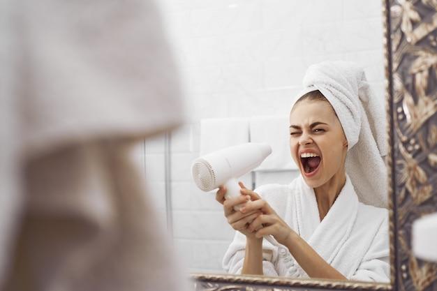 Uma mulher de roupão de banho na frente de um espelho olha para o rosto dela