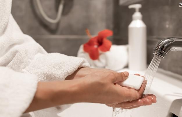 Uma mulher de roupão lava as mãos com sabão em água corrente da torneira.