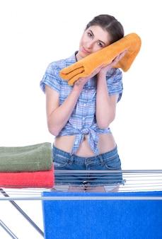 Uma mulher de sorriso que põe toalhas para secar.