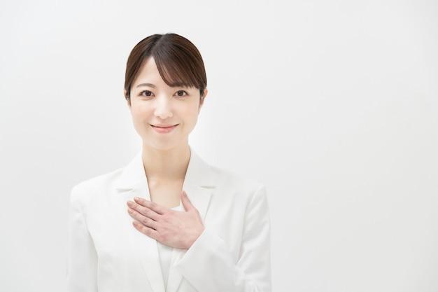 Uma mulher de terno branco em uma pose de alívio