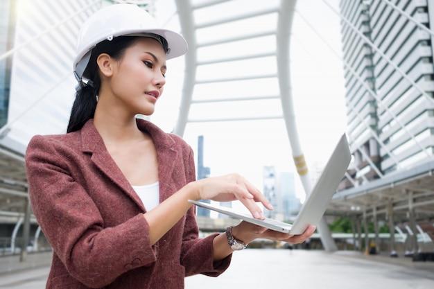 Uma mulher de trabalho asiática confiante está usando um capacete e está trabalhando em um laptop em pé ao ar livre.