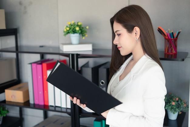Uma mulher de trabalho em terno branco está trabalhando no escritório. ela é uma boa aparência e inteligente gerenciar