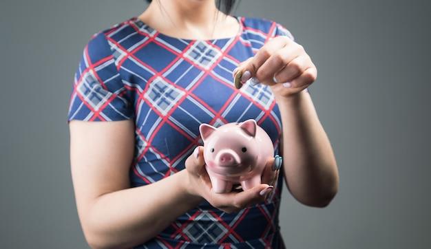 Uma mulher de vestido joga uma moeda em um cofrinho