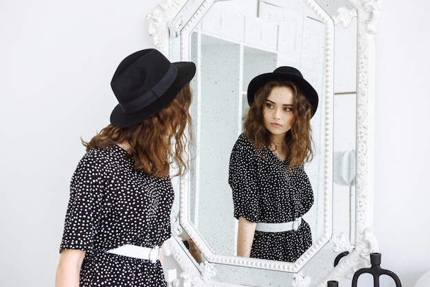 Uma mulher de vestido preto e chapéu se olha no espelho e vê seu reflexo com muitos pontos pretos como sardas em seu rosto